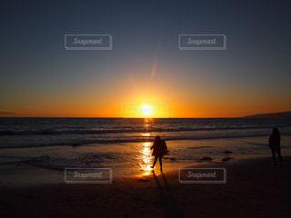 海の横にあるビーチに沈む夕日の写真・画像素材[1028244]