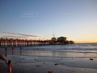 水の体の横に桟橋を歩いている人のグループの写真・画像素材[1028255]