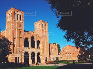 UCLAにある『Royce Hall』大きなレンガの歴史的な劇場とその前の芝生と大学生たちのグループの写真・画像素材[1126807]