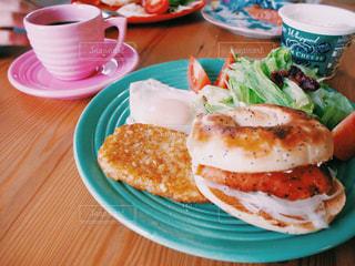 テーブルの上に食べ物のプレート / 時間があるときのお家朝ごはん。ベーグル、スモークサーモン、サラダ、コーヒーをお気に入りのアメリカ製食器でいただきます🇺🇸の写真・画像素材[1144985]