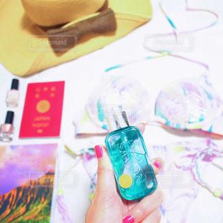 ガイドブックの表紙がきれいなサンセットタイムの写真。それを眺めながら、思わずひとりで海外旅行計画を妄想✈️ パスポート、日焼け対策、水着、ネイル、それとわたしの今一番のお気に入りのジェル香水ローズシャボンも一緒に♡飛び散らないタイプの香水だから使いやすい!きっと旅先でも使っちゃう☺︎の写真・画像素材[1175898]