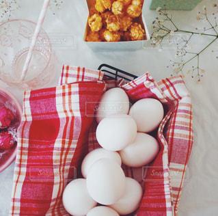 テーブルの上の白いたくさんの卵と赤チェック柄の写真・画像素材[1192983]