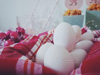 にわとりの白い卵 × 赤チェック柄の写真・画像素材[1193058]