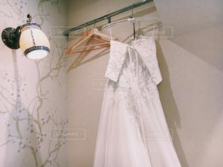 壁に掛かっているウェディングドレス 結婚式 お支度 メイクアップの写真・画像素材[1231202]