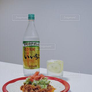 いいちこ 下町のナポレオン いいちこのある時間 いいちこ女子 iichiko / レモネード × ソーダ割り × 輪切りレモン tacos タコスと一緒に / 料理とテーブルの上の瓶のプレートの写真・画像素材[1268602]