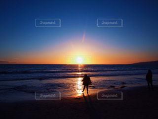 サンタモニカ ビーチ 夕日 夕陽 サンセット 空 女の子 /  バック グラウンドで夕焼けのビーチに立っている人の写真・画像素材[1268687]