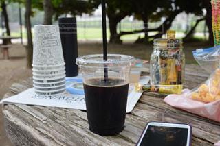 ピクニック用のテーブルの上に座ってコーヒー カップの写真・画像素材[1294222]