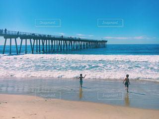 こども 2人 後ろ姿 海 夏 水の体の横にビーチの上を歩く人の写真・画像素材[1393322]