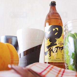 黒伊佐錦 クロイサ 芋焼酎 クローズ ボトルのオレンジ ジュースのガラスの写真・画像素材[1442963]