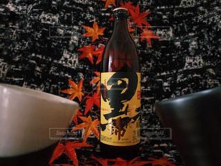 黒伊佐錦 芋焼酎 本格 焼酎 秋 近くのテーブルの上に花瓶の横にあるボトルをの写真・画像素材[1452183]