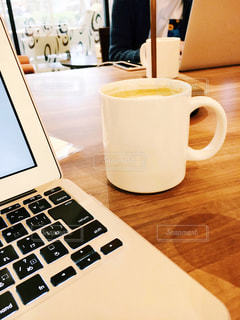 カフェでコーヒーを飲みながらパソコン作業中 ノマドワーカーの写真・画像素材[1584695]