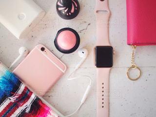 テーブルの上にある小物 アイテム スマホ スマートウォッチ 財布 リップ ピンクの写真・画像素材[1671374]