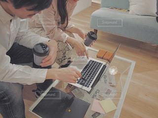 ラップトップ コンピューターを使用してテーブルに座って女と男の写真・画像素材[1815589]