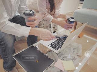 ラップトップ コンピューターを使用してテーブルに座っている女性の写真・画像素材[1815631]