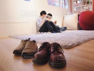 いくつかの靴で、テーブルに座っている人の写真・画像素材[1816427]