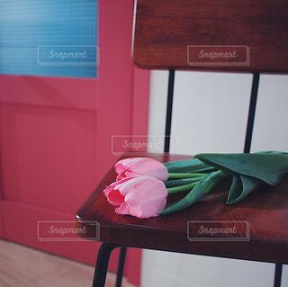 近くに木製のテーブルの上に座っている赤い椅子のアップの写真・画像素材[1819639]