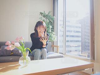窓の前のテーブルに座っている女性の写真・画像素材[1830089]