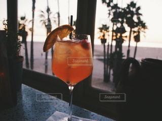 窓の横にオレンジジュースを一杯の写真・画像素材[2375966]