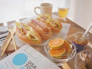 テーブルの上に座っているホットドッグのトレイの写真・画像素材[2501222]