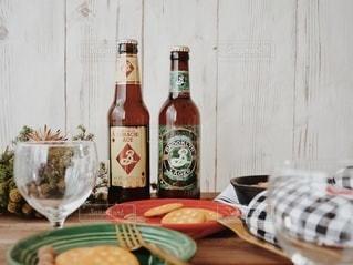 木製のテーブルの上に座っているワインのボトルの写真・画像素材[2828501]
