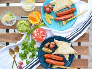 食べ物の皿をテーブルの上に置くの写真・画像素材[3220065]