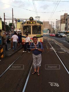 電車の横の通りを歩く人々 のグループ - No.718925