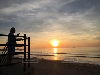 ビーチでの背景の夕日に人々 のカップルの写真・画像素材[1302453]