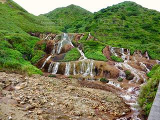みどりを縫う岩肌と白糸のような滝の写真・画像素材[1491518]