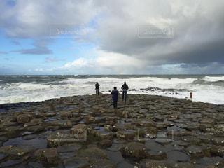 岩の多いビーチに立つ人々 のグループの写真・画像素材[787148]