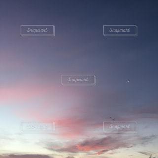 バック グラウンドで夕日を持つ男の写真・画像素材[962809]