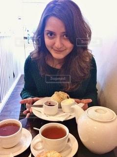 紅茶を飲みながらテーブルに座っている女性の写真・画像素材[2699069]