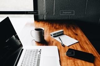 木製のテーブルの上に座っているラップトップコンピュータの写真・画像素材[3295908]
