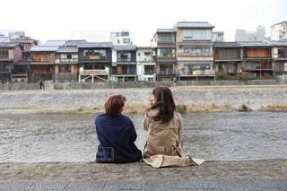 建物の前にあるベンチに座っている人の写真・画像素材[909955]