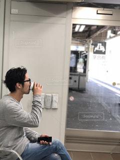携帯電話で話している椅子に座っている人の写真・画像素材[1522570]