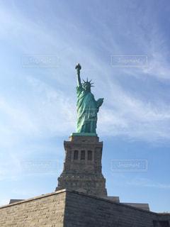 建物の側に時計と大きな背の高い塔の写真・画像素材[1015840]