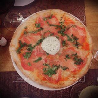木製のテーブルの上に座ってピザの写真・画像素材[1216606]