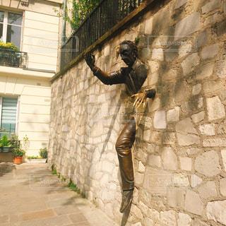 レンガ造りの建物の前に立っている人の像の写真・画像素材[2231316]