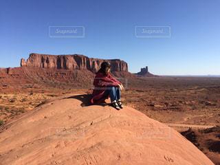砂漠の丘を歩く男の写真・画像素材[1026508]