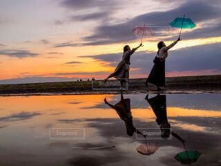 夕日傘を持っている人の写真・画像素材[3707878]