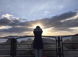 女性,海,空,後ろ姿,未来,夕陽,夢,ポジティブ,キャッチ,目標,雲の隙間,太陽の光,可能性,受け取る