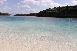 水の体の横にある砂浜のビーチの写真・画像素材[899713]