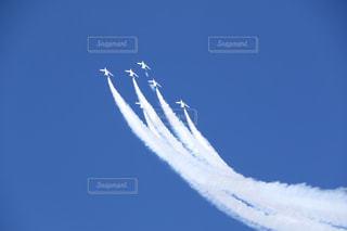 青い空を飛んでいるジェット戦闘機の写真・画像素材[1104469]