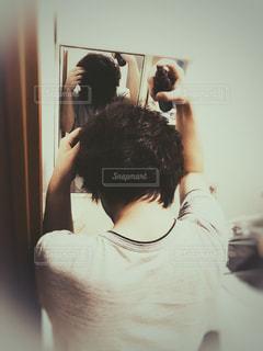 カメラにポーズ鏡の前に立っている人の写真・画像素材[1524121]