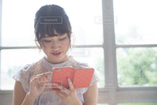窓の前に座っている女の子の写真・画像素材[2309320]