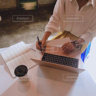 ノートパソコンを持ってテーブルに座っている人の写真・画像素材[2505665]