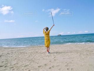 海の隣の砂浜の上に立つ人の写真・画像素材[2776788]
