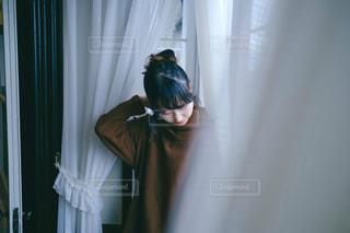 カーテンの前に立っている人の写真・画像素材[3314798]