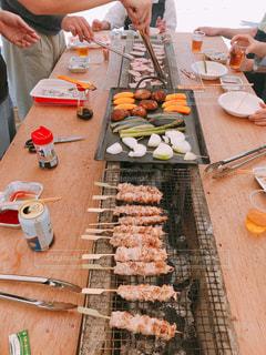 テーブルの上に食べ物を準備する人々 のグループの写真・画像素材[1214418]