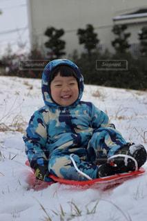 雪の中で座っている小さな男の子の写真・画像素材[1754917]