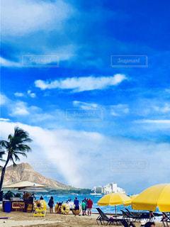 ビーチ パラソルに座っている人々 のグループの写真・画像素材[1386724]